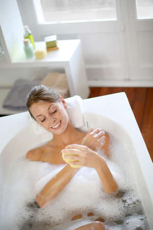 bathroom woman: Beautiful woman using bath sponge