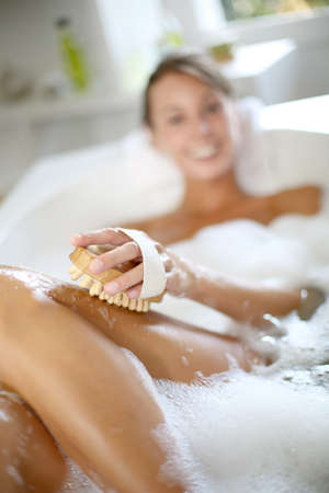 Woman in bathtub scrubbing her legs photo