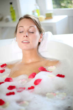 Beautiful woman relaxing in bath with rose petals photo