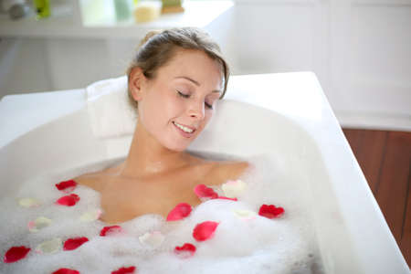 bathtub: Beautiful woman relaxing in bath with rose petals