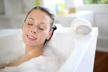 Woman relaxing in bathtub with eyes closed photo