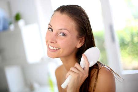 tratamiento capilar: Retrato de ni�a sonriente cepillarse el cabello Foto de archivo