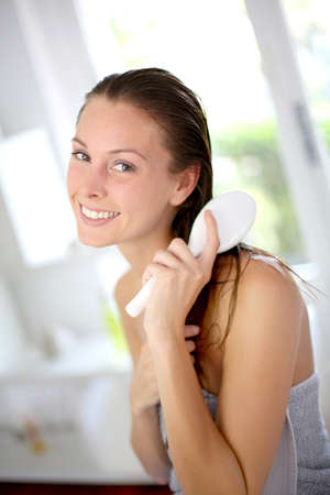 wet hair: Portrait of smiling girl brushing her hair