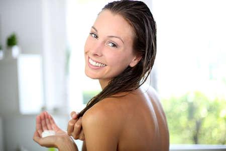 champu: Hermosa mujer poniendo acondicionador en el pelo