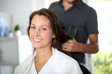 Woman having her hair dried by hairdresser photo