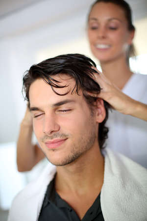 Hairdresser doing head massage to customer photo