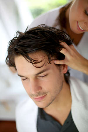 Hairdresser doing hair massage to customer photo