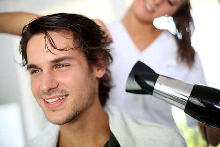 hair dryer: Hombre joven en el sal�n de belleza con el pelo secado Foto de archivo