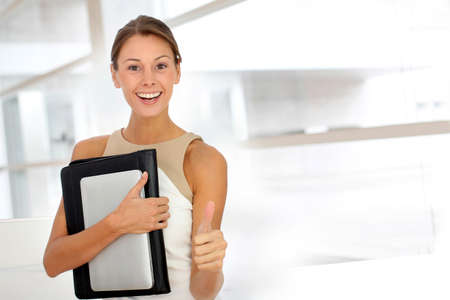 Cheerful businesswoman showing thumb up photo