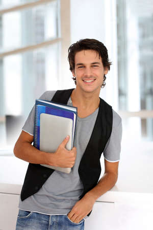 handsome student: Cheerful college student standing in hall