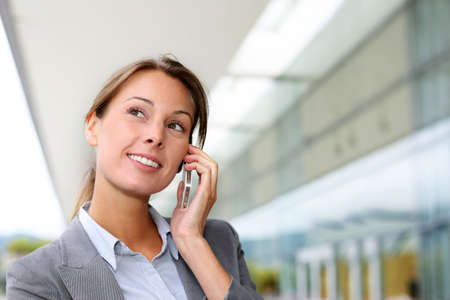 telephone saleswoman: Smiling businesswoman talking on mobile phone Stock Photo