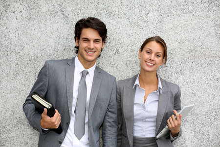 Cheerful business people standing on grey background Stock Photo - 15384337