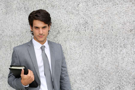 Closeup of young businessman leaning on wall photo