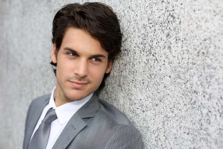 gray suit: Closeup of handsome businessman leaning on wall