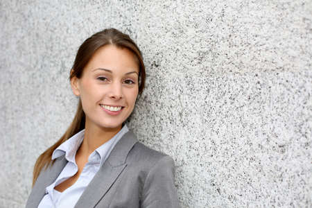 Smiling executive woman leaning on grey wall Stock Photo - 15384318