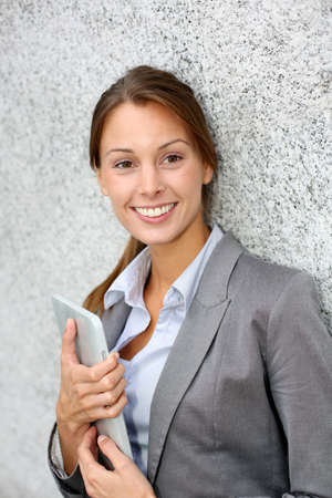 Smiling executive woman leaning on grey wall Stock Photo - 15384324