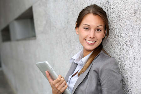 Smiling executive woman leaning on grey wall Stock Photo - 15384201