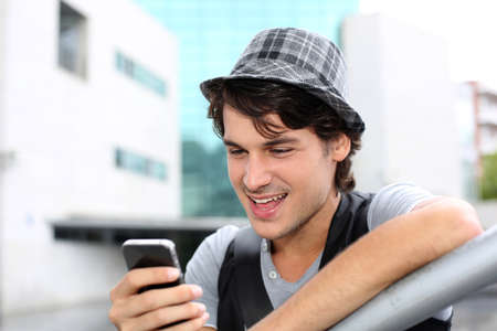sending: Portrait of young guy sending message with smartphone Stock Photo