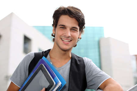 internship: Cheerful student standing outside college building