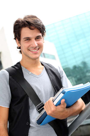 Cheerful student standing outside college building photo