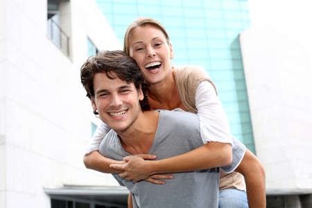 young couple smiling: Man giving piggyback ride to girlfriend