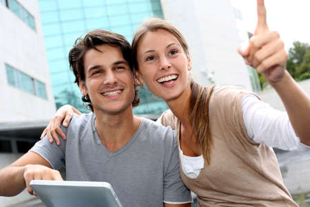 Students using tablet outside and pointing at something Stock Photo - 15384204