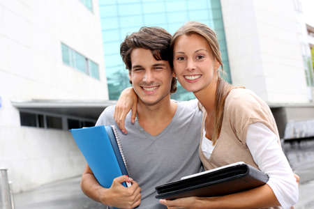 Cheerful couple of students standing on college campus photo