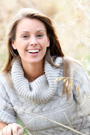 woman sweater: Beautiful woman standing in country field Stock Photo
