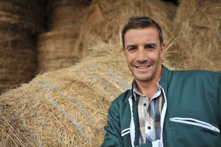 men 45 years: Portrait of cheerful farmer standing in front of hay rolls Stock Photo