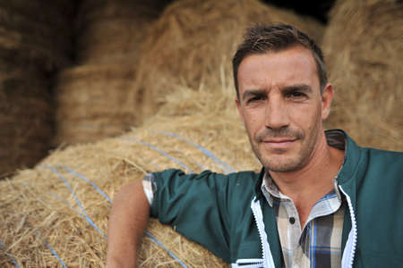 Portrait of cheerful farmer standing in front of hay rolls photo