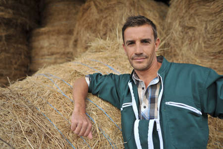 Portrait of cheerful farmer standing in front of hay rolls Stock Photo - 15435431