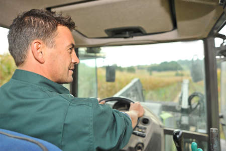 45 years old: Farmer driving tractor in corn field