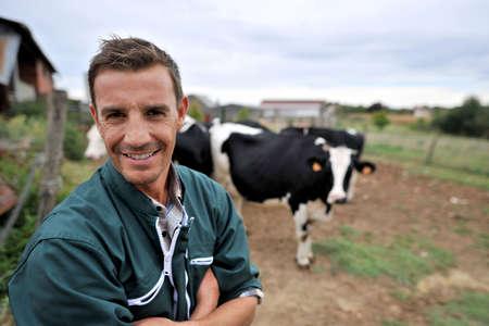 Smiling cow breeder standing in in front of cow herd Stock Photo - 15427768