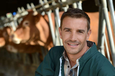 Portrait of smiling farmer with cows in background photo