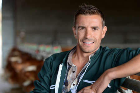 Portrait of smiling herdsman standing in barn photo