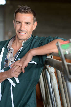 Portrait of smiling herdsman standing in barn Stock Photo - 15427789
