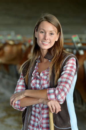 Smiling farmer woman standing in barn photo