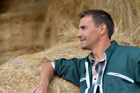 45 years old: Portrait of smiling farmer standing by haystacks