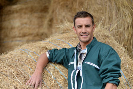 herdsman: Portrait of smiling farmer standing by haystacks