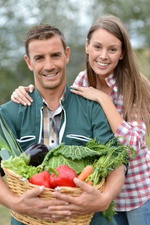 peasant farming: Portrait of couple of farmers holding basket of vegetables