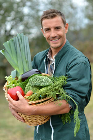 Portrait of smiling farmer holding vegetables basket photo