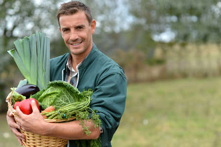 farmer: Portrait of smiling farmer holding vegetables basket