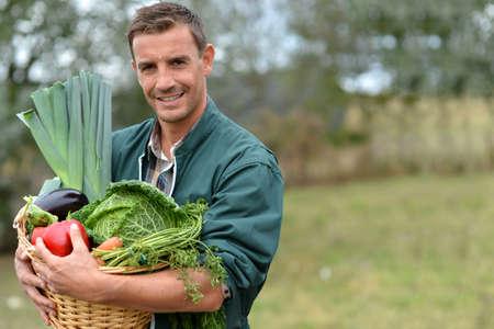 granjero: Retrato de la sonrisa agricultores titulares cesta hortalizas