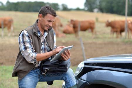 veterinario: Criador de granja con tableta digital Foto de archivo