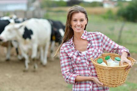 農家: 新鮮なミルクのボトルを運ぶ若い農夫の笑みを浮かべてください。