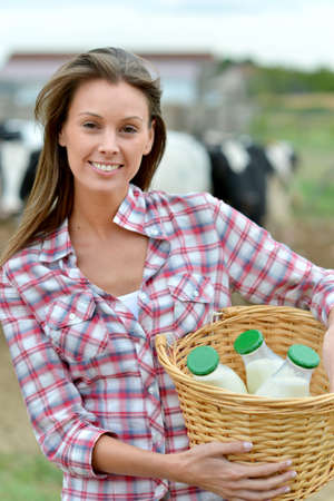 cattle breeding: Smiling young farmer carrying bottles of fresh milk Stock Photo