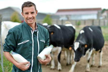 cattle: Granjero que se coloca delante de la manada con botellas de leche Foto de archivo