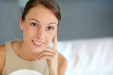 Portrait of attractive woman sitting in couch Stock Photo - 15611097