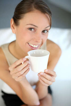 hair tied: Attractive woman relaxing in sofa with cup of tea