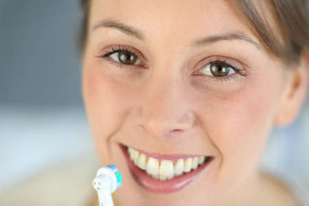 toothy: Closeup on womans toothy smile brushing her teeth